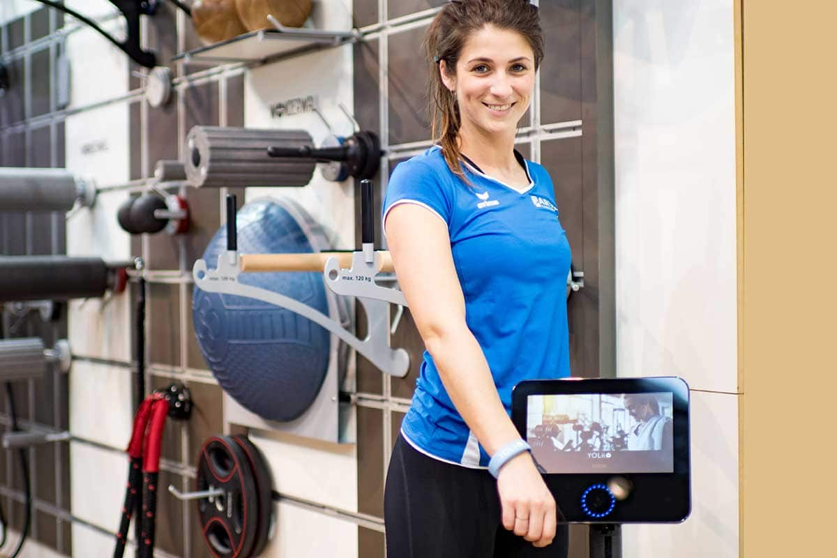 Young woman in sportswear with YOLii RFID wristband on monitor